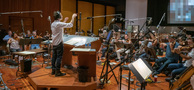 Composer/conductor Jeff Russo checks with the playback as the orchestra records