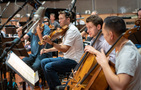 The viola and cello sections watch the conductor