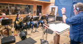 Orchestrator Pete Anthony conducts the winds and brass session
